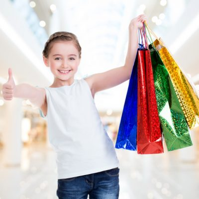 Pretty smiling little girl with shopping bags with thumb up sign in the shop